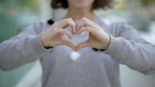 beskuren bild av kvinnan att göra hjärtat form med händerna - hjärtform bildbanksvideor och videomaterial från bakom kulisserna