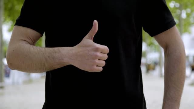 vídeos de stock, filmes e b-roll de tiro cortado do homem novo que mostra o polegar acima ao ar livre. - camiseta preta