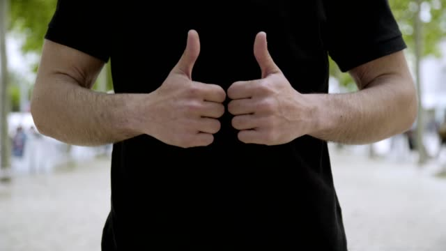 Cropped shot of young man showing thumbs up outdoor.