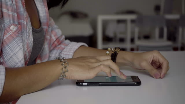 Cropped shot of young woman wearing pink checkered shirt sitting at table and using smartphone. video