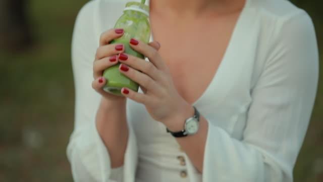 クロップ認識不可能女の人を飲む緑のスムージー屋外 - ローフード点の映像素材/bロール