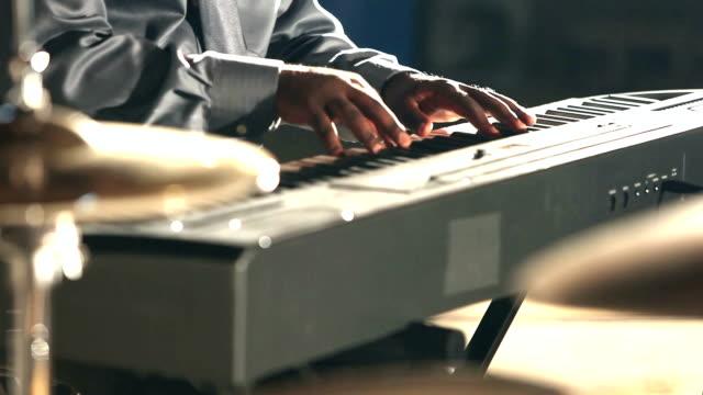 Cropped view of black man playing electronic keyboard