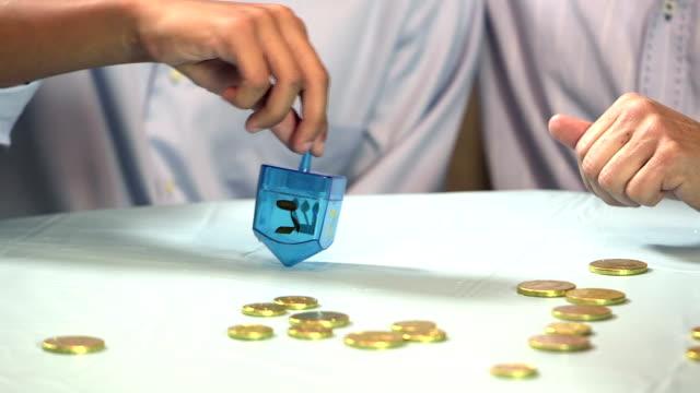 vídeos y material grabado en eventos de stock de recortada visión de padre e hijo jugando trompo - hanukkah
