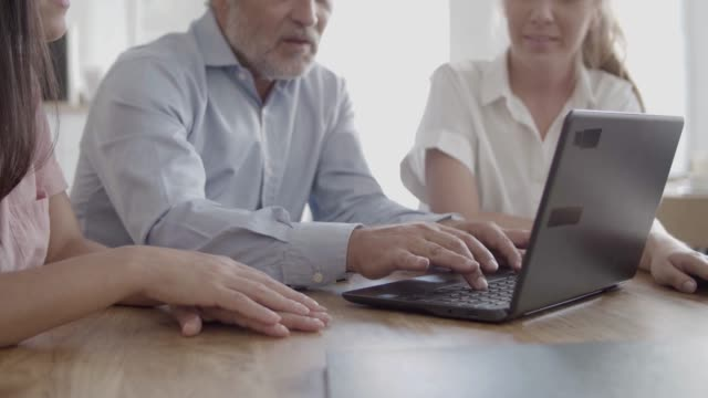 Cropped view of senior businessman typing on laptop keyboard