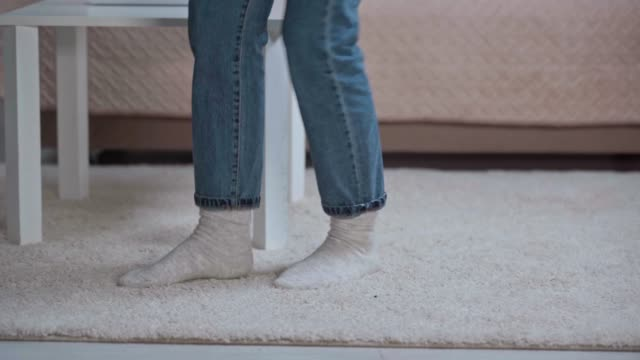 cropped view of woman stumbling over table leg and injuring foot