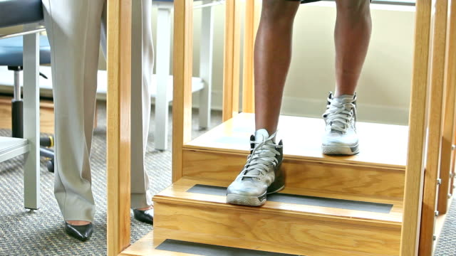 cropped view, physical therapist with patient on training stairs - fisioterapia video stock e b–roll