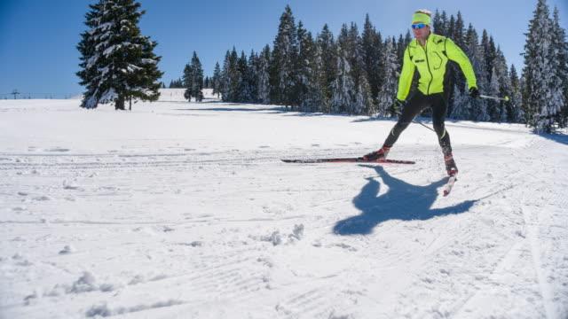 Cross country skier full power skate skiing uphill video