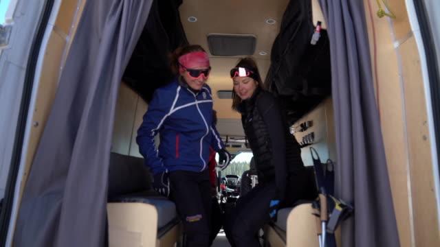 stockvideo's en b-roll-footage met langlaufers die een pauze nemen, opwarmen in een conversie camper van - caravan