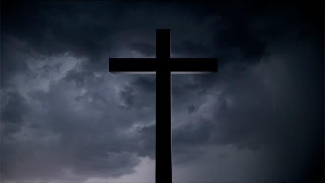 Cross illuminated by thunderstorm video