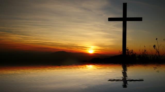 vídeos de stock e filmes b-roll de cross of jesus christ near water with sunset and peaceful mood. - filosofia