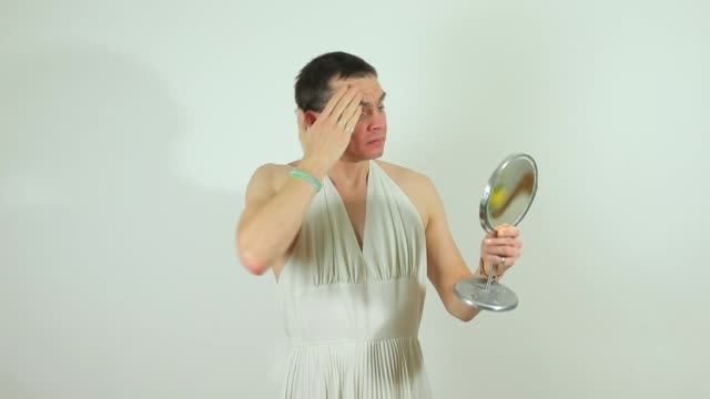 cross-dresser in white dress rubs cream on face video