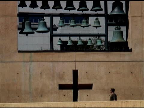 vídeos y material grabado en eventos de stock de cruzar la izquierda: hombre camina cruz y campanas pasado gigante - gran inauguración