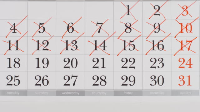TOP VIEW: Crossing out a numbers in a paper calendar - Stop motion animation