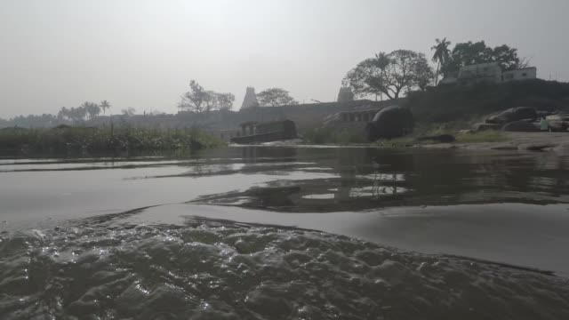 Crossing river in Hampi, India. Smooth shot passes Shiva lingams in water, islands, grass, and men bathing an elephant. video