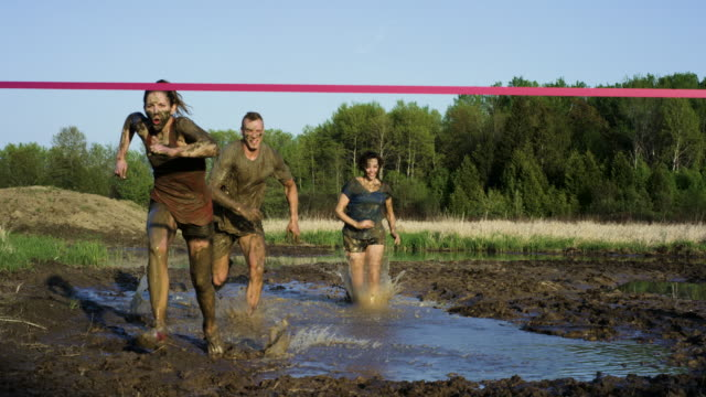 Crossing the Finish Line Three young adults are participating in a mud run. In this video they are running by the camera finishing the race as they cross the red tape finish line. conquering adversity stock videos & royalty-free footage