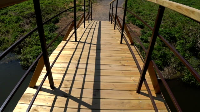 Crossing wooden bridge over the river, point of view.