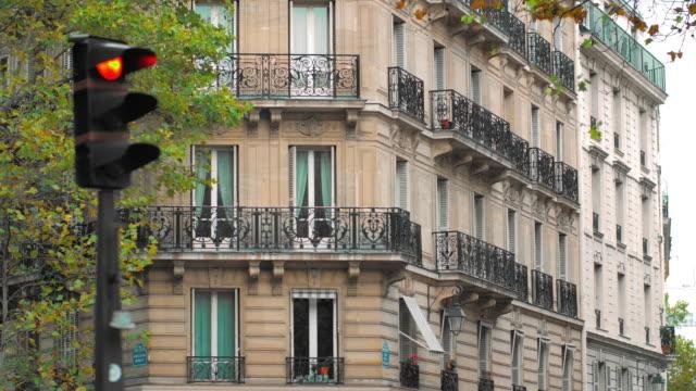 vídeos de stock e filmes b-roll de crossroads, traffic lights and a typical french building in the center of the capital. paris, france - enfeitado