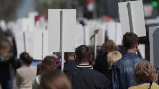 Crowd activists at a rally with posters are on the road walking banner France 4K
