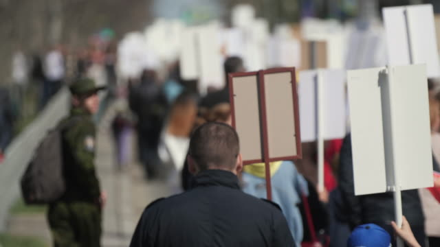 Crowd activists at a rally with posters are on the road walking banner Europe 4K video