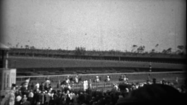 1935: crowd at horse track race watching horses come out to compete. - horse racing filmów i materiałów b-roll