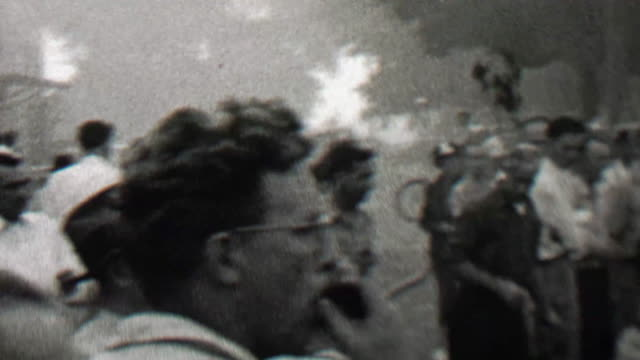 1939: Crowd lookiloos gathers to watch the burning small town building. video