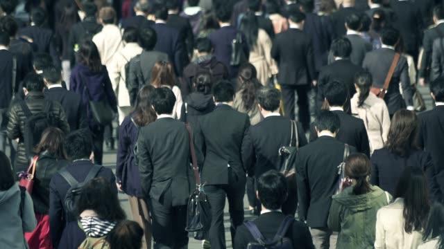 朝新宿東京に仕事に行くビジネスマンの群衆 - ビジネスマン点の映像素材/bロール
