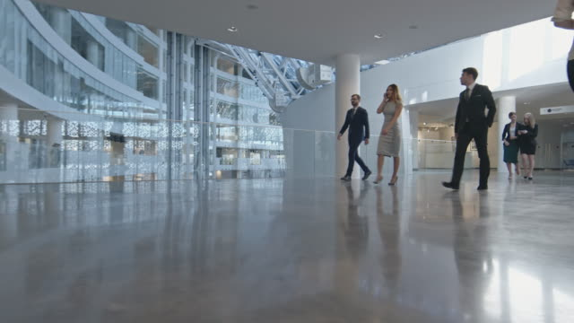 crowd of businesspeople walking through lobby - contemporary architecture stock videos & royalty-free footage