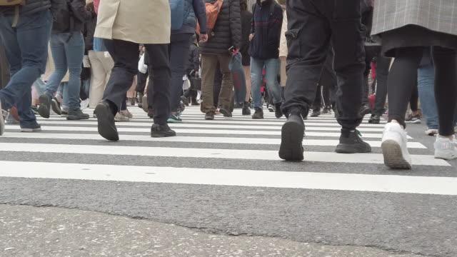 skara pendlare korsar shibuya crossing i tokyo - människofot bildbanksvideor och videomaterial från bakom kulisserna