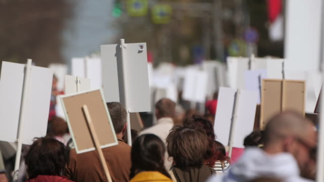 a crowd of demonstrators walking agitating on strike against the government. - climate change video stock e b–roll