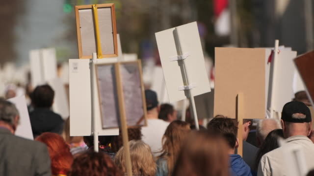en skara demonstranter går agitera på strejk mot regeringen. - etnicitet bildbanksvideor och videomaterial från bakom kulisserna