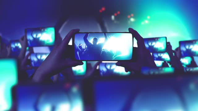 A crowd of fans is shooting a concert on smartphones.