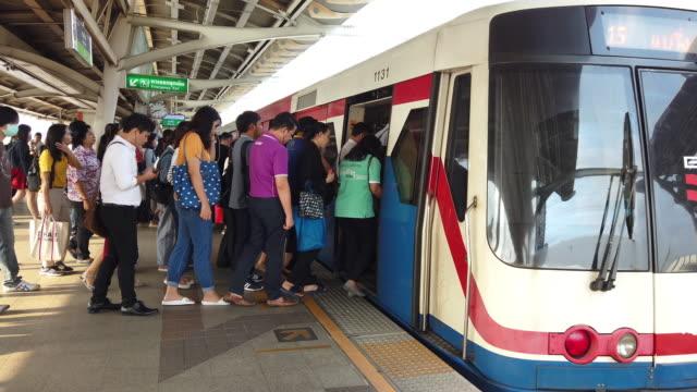 vídeos y material grabado en eventos de stock de una multitud de lugareños y turistas se alinean para abordar el tren aéreo bts en bangkok, tailandia - bangkok