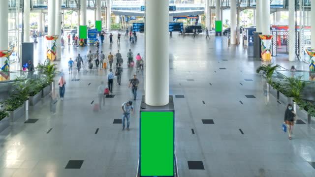 tl: crowd of passengers walking with green screen of billbroad in the kualanamu international airport, indonesia - коммерческий знак стоковые видео и кадры b-roll