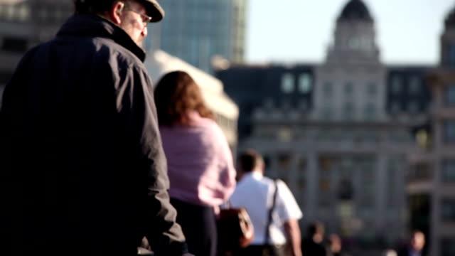 pedonale folla di pendolari che sfrecciano su london bridge lontano dalla telecamera - london bridge inghilterra video stock e b–roll