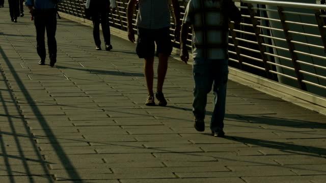 folla di pedoni camminare sulla golden jubilee bridge, londra. - london bridge inghilterra video stock e b–roll