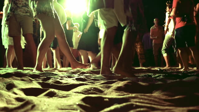 Crowd of people dancing at night during beach party