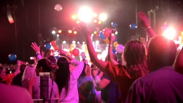 Crowd of people dancing raising hands at a concert - multi-colored balloons flying around the concert hall