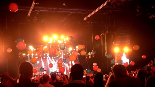 Crowd of people having fun at a concert with balloons flying around the concert hall
