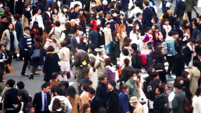 menge von menschen zu fuß in die kreuzung shibuya in tokio - überweg warnschild stock-videos und b-roll-filmmaterial