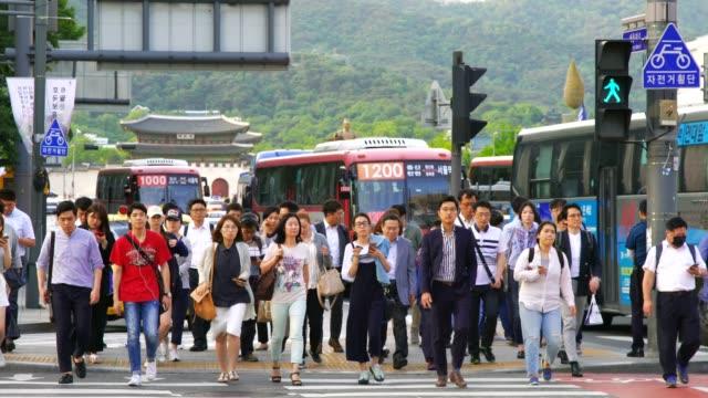 vídeos de stock, filmes e b-roll de multidão de pessoas andando durante o semáforo com gwanghwamun plaz em seoul, coreia do sul - coreia