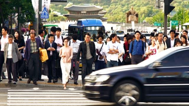 vídeos de stock, filmes e b-roll de multidão de pessoas andando durante o semáforo com gwanghwamun plaz em seul - coreia