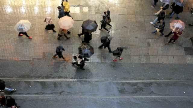 Crowd of people walking with umbrellas in rain on Istiklal Street, Beyoglu, Istanbul, Turkey. video