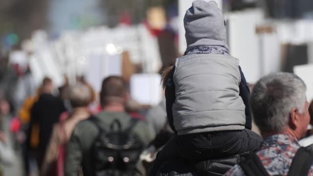 en skara demonstranter gå längs banderoller med grabben på strejk på en stadsgata - sociala frågor bildbanksvideor och videomaterial från bakom kulisserna