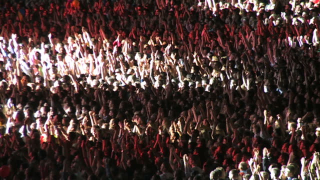 crowd of spectators on the stadium waving hands and applauding in the spotlight video