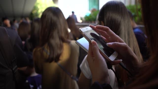 vidéos et rushes de 4k foule de touristes utilisant le smartphone dans une file d'attente pour le tram de train victoria peak - faire la queue