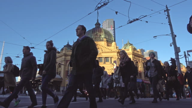crowd people crossing road at flinders street station, melbourne - melbourne stock videos & royalty-free footage