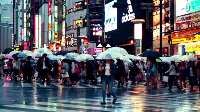 人群中的人抱著雨傘橫穿馬路在澀谷, 而下雨, 黃昏黃昏 - 澀谷交叉點 個影片檔及 b 捲影像