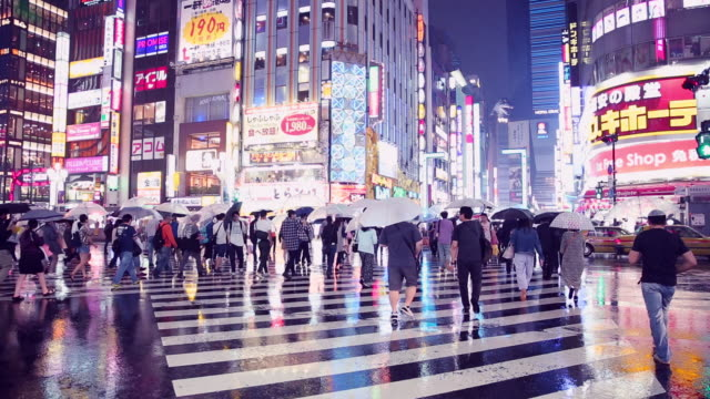 Crowd people walking and crossing road in the city while raining