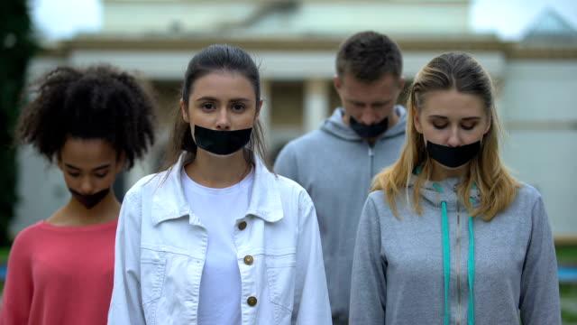 crowd-performance mit verklebtem mund, verletzung der sprachfreiheit, zensur - dominanz stock-videos und b-roll-filmmaterial