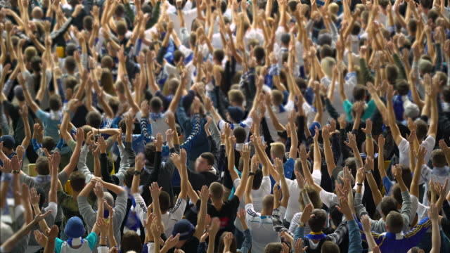 crowd raising their hands in support of football soccer team, waiting for score - дворец спорта стоковые видео и кадры b-roll